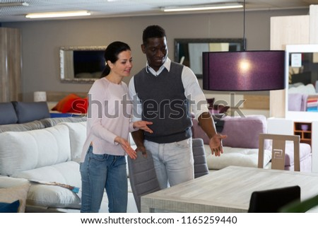 African man with his wife are choosing new table for living room in the store.