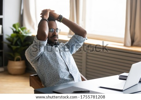 African man with inner tension feels nervous wait for important e-mail search solution sitting at desk alone. Unmotivated lazy employee leaned on office chair resting at workplace looks at pc screen