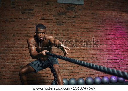 African man with naked torso doing fitness workout in cross fit gym. Shirtless strong athlete being concentrated on the exercise with battle rope requiring increased effort and strength.