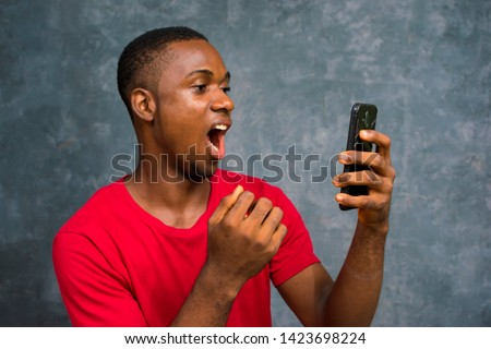 African man with surprised face holding his smartphone with his mouth opened . guy looking at his phone after receiving a shocking news