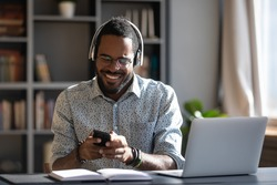 African man worker or student sit at desk distracted from study or work hold smartphone wear headphones hearing voice audio message from friend, enjoy free time use modern gadget wireless tech concept