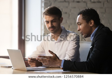 African manager mentor consulting teaching caucasian client intern showing new online project give presentation on laptop, black advisor speaking helping customer explaining deal pointing at computer