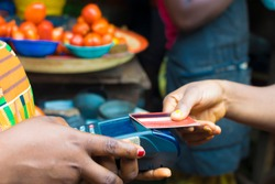 African market women making transition with Point of sale machine and a Credit card. Woman paying bills online using bank card in a local market
