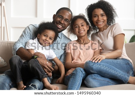 African married couple and little adorable children embracing sitting together on couch in living room at home looking at camera photographed for memory, happy mixed-race full family portrait concept