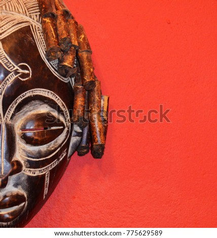 African mask on a red isolated background. #775629589