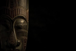 African mask over black background with copy space