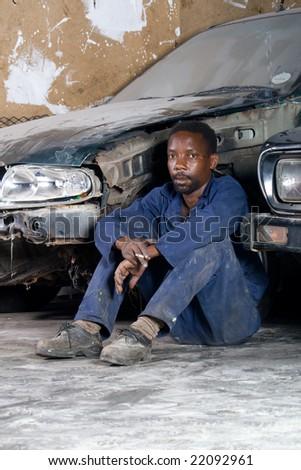 african mechanic resting in garage during lunch break