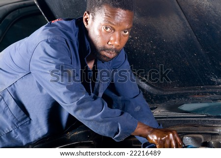 african mechanic working on a broken down vehicle