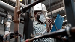 African mechanical supervisor in safety mask doing inspection on plant. Afro-american inspector in hardhat and protective mask with clipboard checking pipe system at manufacturing plant