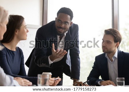 African mentor gives valuable advice to staff members during workshop training. Diverse workmates brainstorming share ideas and creative thoughts, team listen leader of project during meeting concept