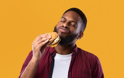 African Millennial Guy Smelling Tasty Burger Standing On Yellow Studio Background. Black Man Enjoying Eating Hamburger. Unhealthy Nutrition Habit, Overeating. Junk Food Lover Concept