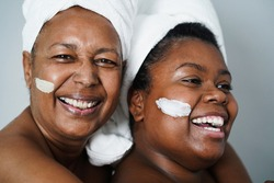 African mother and daughter doing beauty treatment at home using skin mask - Body care and family concept - Focus on right girl mouth