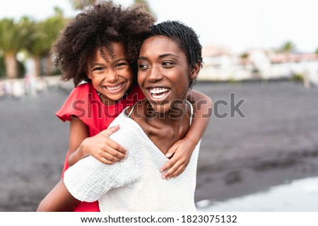 African mother and daughter having fun on the beach - Focus on mom's face