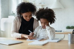 African mother helps with task little schoolgirl daughter do together schoolwork, parent explain subject, focused child listen to mum sit at table at home in kitchen. Education, homeschooling concept