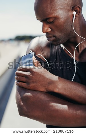 African muscular athlete listening to music. Male model listening to music from his mobile phone on armband.