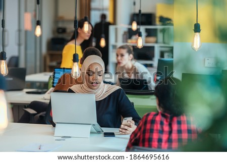 African muslim girl wearing hijab working on a laptop in a modern startup company. While being gossiped by her european coworkers. Photo stock ©