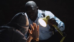 African officer interrogating man suspected of crime glowing light of lamp into face. Afro-american sheriff questioning arrested man in dark room of police department