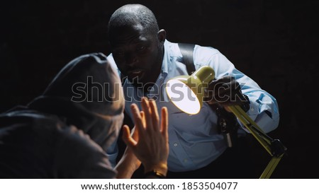 African officer interrogating man suspected of crime glowing light of lamp into face. Afro-american sheriff questioning arrested man in dark room of police department Stock photo ©