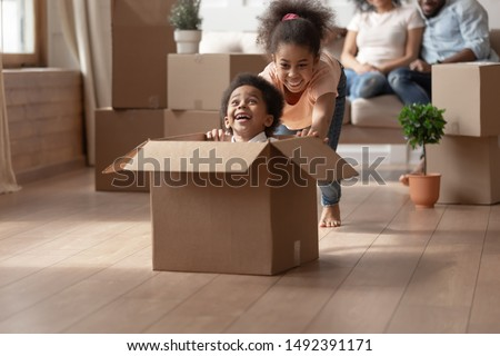 African older sister riding younger cute brother who is sitting in cardboard box, on background big carton boxes stuff and parents sitting on couch enjoy new modern house resting at moving day concept Сток-фото ©