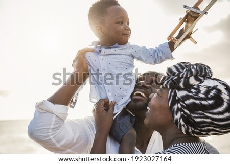 African parents and little son having fun with wood airplane on the beach - Family people having fun together outdoor - Main focus on woman face Stockfoto ©