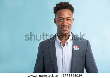 African patriotic politician pinned vote button on suit, elections in America 2020, blue background, copy space Stock photo ©