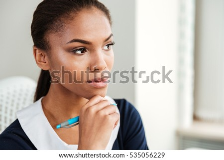 African pensive business woman in dress standing in office and holding hand near the face #535056229