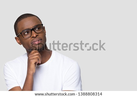 African pensive guy isolated on grey blank looking aside copy space touch chin lost on thoughts thinking businessman in white t-shirt glasses planning business decision dreaming future success concept