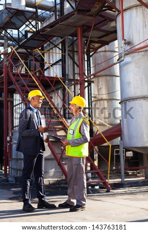 african petrochemical manager in discussion with plant worker outdoor