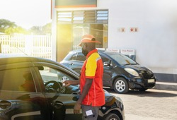 African petrol attendant checking temperature of the driver with an infrared thermometer at a gas station in Botswana