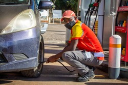 African petrol attendant checking tire presure at a gas station in Botswana