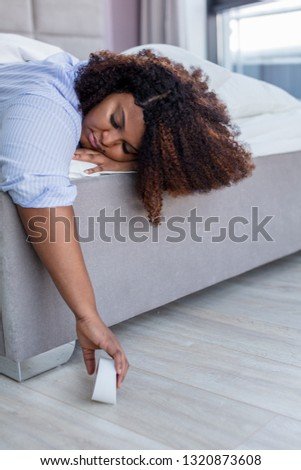 african plump girl turning off the alarm clock as she wants to sleep longer, close up photo.