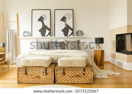 African posters, wicker boxes, fireplace and double bed with patterned pillows in a boho bedroom interior #1073122067