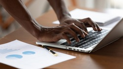 African project manager typing on pc close up view businessman hands and device, document with graphs charts lie on office desk. Business app usage, forecasting, financial report preparation concept