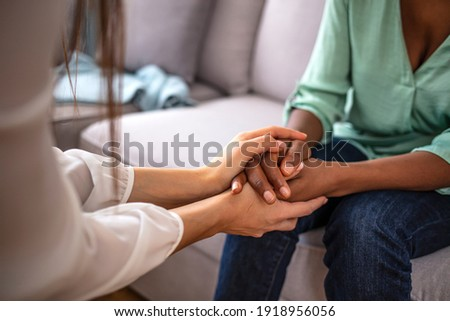 African psychologist hold hands of girl patient, close up. Teenage overcome break up, unrequited love. Abortion decision. Psychological therapy, survive personal crisis, individual counselling concept