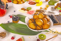 African Puff Puff on white bowl on decorated table with fruits.