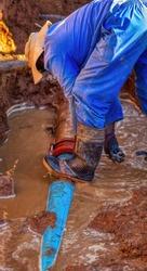 African repairman attending to the city water supply repairs in Gaborone Botswana