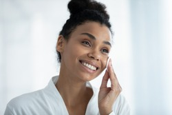 African 30s woman looking in mirror do morning routine moisturizing and cleanses skin use cotton pad and micellar water or milk close up head shot. Self-care, personal hygiene, daily procedure concept