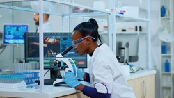 African scientist checking sample of virus using microscope in modern lab. Multiethnic team examining vaccine evolution using high tech for scientific research of treatment development against covid19
