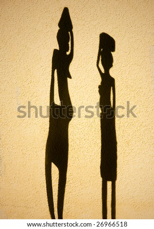 African shadow silhouettes against a plastered wall