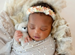 African sleeping baby holding toy in little hands