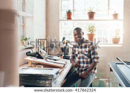 African small business owner sitting in his well lit studio