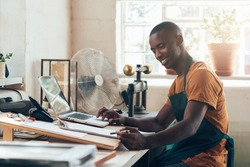 African small business owner smiling with paperwork and laptop