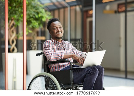 African smiling man sitting in wheelchair and using laptop computer in the mall ストックフォト ©