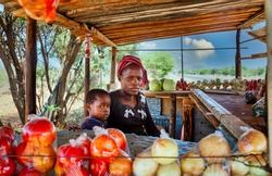 african street vendor, mother and child, selling onions, cabbage, tomatoes.