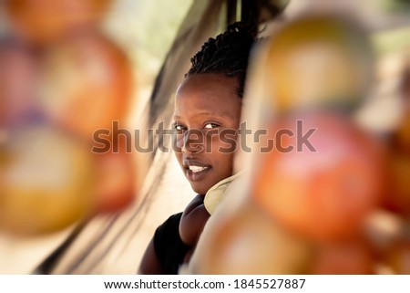 african street vendor, mother holding her child between the bags of tomatoes Сток-фото ©