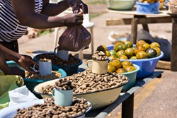 african street vendors selling peanuts, monkey oranges, beans, kumquats oranges
