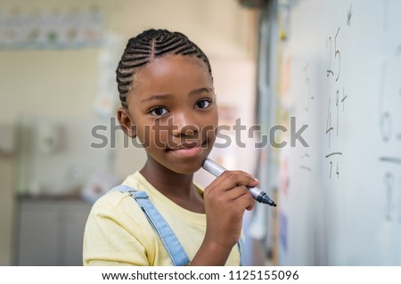 African student girl doing math problems on white board. Portrait of black schoolgirl doing math addition at whiteboard in classroom. Closeup face of schoolgirl looking at camera.