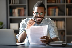 African student guy sitting at desk holding papers printed tasks perform test prepares for entrance exams enjoy process of study. Teacher checking assignment homework, company lawyer paperwork concept