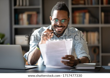 African student guy sitting at desk holding papers printed tasks perform test prepares for entrance exams enjoy process of study. Teacher checking assignment homework, company lawyer paperwork concept ストックフォト ©