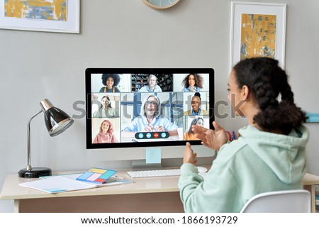 African teen high school girl college student distance learning virtual remote class, group online interactive lesson on video conference call talking with teacher on computer screen studying at home.